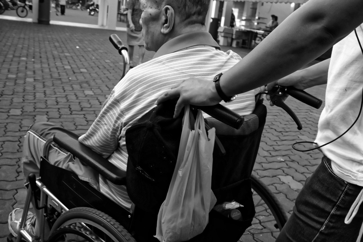 wheelchair_elderly_man_pushed_carer_black_and_white_photo-858183
